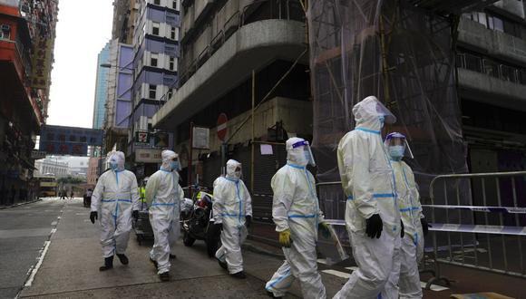 Limpiadores con trajes protectores se reúnen en el área de Yau Ma Tei, en Hong Kong. (Foto: AP / Vincent Yu)
