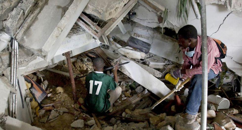 Ciudadanos haitianos usan palas y sus manos para limpiar los escombros en un intento de encontrar a sobrevivientes en el hotel de Montana, que se derrumbó tras el devastador terremoto. (Foto: AFP).