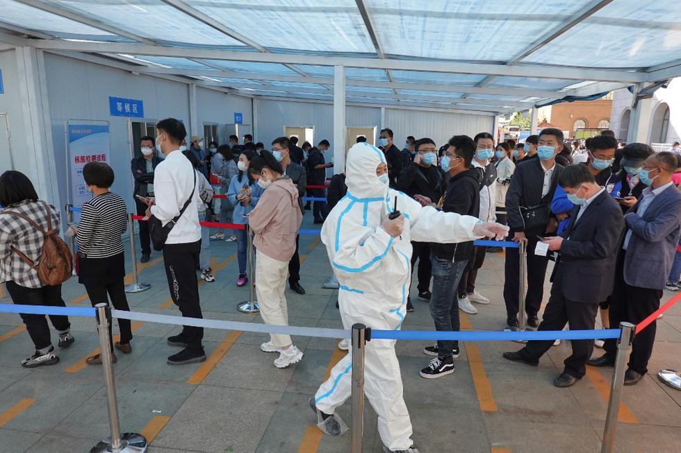 Un trabajador de la salud dirige a las personas mientras se alinean para hacerse la prueba del coronavirus COVID-19. (STR / AFP)