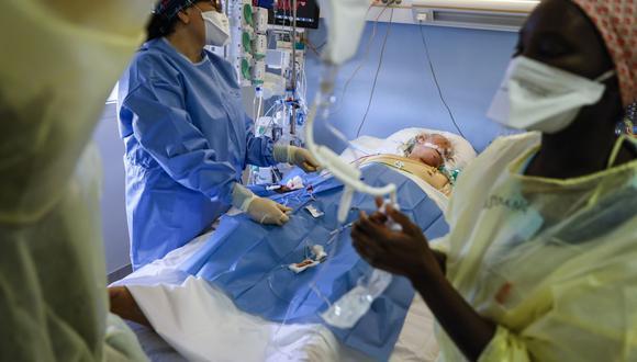 Un paciente infectado con el nuevo coronavirus (Covid-19) es atendido por una enfermera y un anestesiólogo en una sala de cuidados intensivos del Hospital Privado Estree en Stains, en las afueras de París. (Foto de Thomas SAMSON / AFP).