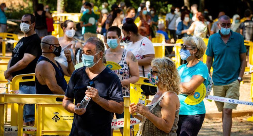 Un centenar de personas se congregaba el jueves frente a un puesto médico de campaña instalado en Ripollet, al norte de Barcelona, para hacer el despistaje gratuito de coronavirus. (EFE/ Enric Fontcuberta).