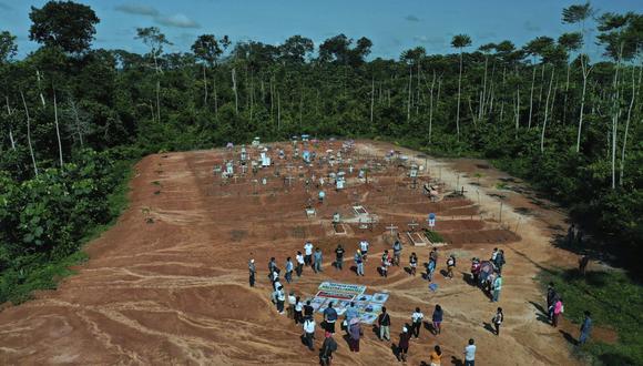 Familiares de personas que murieron por COVID-19 se reúnen junto a una fosa común clandestina en las afueras de Iquitos, el sábado 20 de marzo del 2021. Las autoridades locales aprobaron entierros masivos de víctimas de la pandemia, pero nunca se lo dijeron a las familias que creían que sus seres queridos estaban enterrados en el cementerio local cercanos y solo meses después descubrieron la verdad. (Foto: AP / Rodrigo Abd)