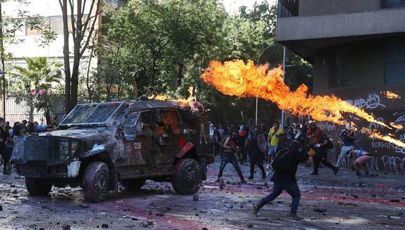 """Manifestantes se enfrentan a la policía en la Plaza Italia de Santiago de Chile, rebautizada popularmente como """"Plaza Dignidad"""", durante el primer aniversario de las protestas que sacudieron todo el país austral. (EFE/Elvis González)."""