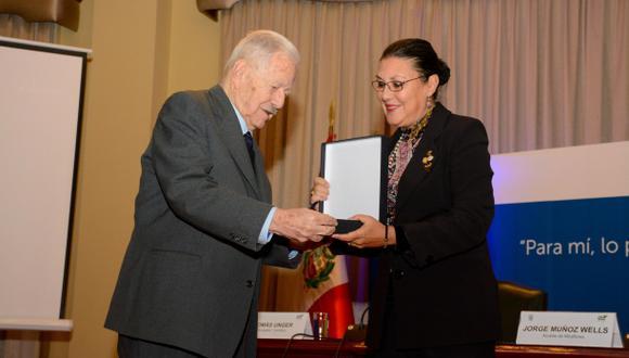 El ingeniero Tomás Unger recibe de mano de Fabiola León-Velarde, presidenta del Concytec, un reconocimiento por su dilatada carrera de divulgador científico. (Concytec)