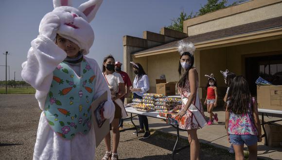 En la foto tomada el 27 de marzo de 2021, voluntarios esperan vehículos como parte de una iniciativa de entrega de regalos de Pascua en la ciudad fronteriza de Roma, en el sur de Texas. (Foto: AFP)