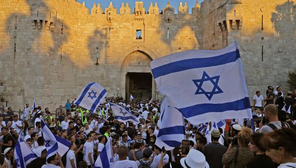 Israelíes levantan banderas durante la Marcha de las Banderas ultranacionalista frente a la Puerta de Damasco en la Ciudad Vieja de Jerusalén, el 15 de junio de 2021. (Foto de Menahem KAHANA / AFP).