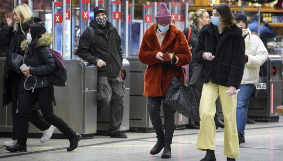 Un grupo de usuarios ingresan a una estación de metro utilizando mascarillas para frenar la propagación del coronavirus, en Estocolmo, Suecia, el pasado 7 de enero de 2021. La Agencia de Salud Pública de Suecia aconseja a los viajeros del transporte público que usen una máscara durante las horas pico. (Jessica Gow / TT News Agency / AFP)