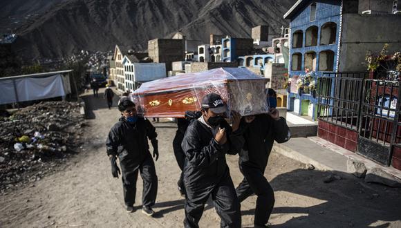 Los trabajadores del cementerio llevan el ataúd de una víctima de COVID-19 en un cementerio en Comas, el 5 de agosto de 2020. (Foto: ERNESTO BENAVIDES / AFP)