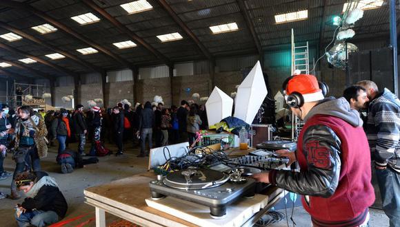 Un DJ toca música durante una fiesta en un hangar en desuso en Lieuron, Francia, en pleno toque de queda por coronavirus. (Foto de JEAN-FRANCOIS MONIER / AFP).