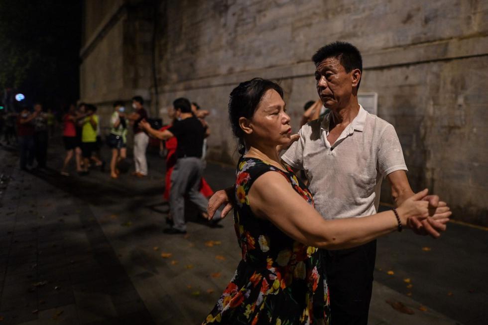 Parejas bailan junto al río Yangtze en Wuhan, provincia de Hubei, China. Imagen del 5 de agosto de 2020. (AFP / Hector RETAMAL).
