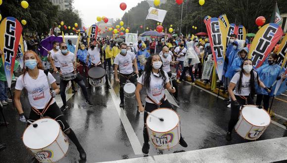 Manifestantes marchan bajo la lluvia este miércoles en Bogotá, Colombia. (EFE/ Carlos Ortega).