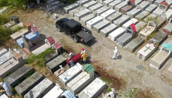 Trabajadores entierran un ataúd en el cementerio de María Canals en las afueras de Guayaquil, Ecuador, uno de los países de Sudamérica más golpeados por el coronavirus. (AFP / Jose Sánchez).