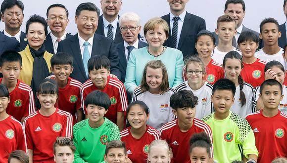German Chancellor Angela Merkel (C) and the President of the People's Republic of China Xi Jinping (4rd L) pose with the players prior to a football match between the U12 teams of Germany and China in Berlin on July 5, 2017.  / AFP / POOL AP / Michael Sohn