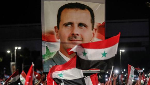 Los sirios ondean banderas nacionales y llevan un gran retrato de su presidente mientras celebran en las calles de la capital, Damasco, un día después de una elección programada para darle al actual presidente Bashar al-Assad un cuarto mandato. (Foto: LOUAI BESHARA / AFP).