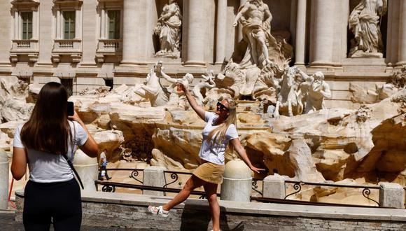 Una persona sin mascarilla posa frente a la Fontana di Trevi, en Roma, Italia, el 28 de junio de 2021. (REUTERS/Guglielmo Mangiapane).