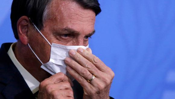 El presidente de Brasil, Jair Bolsonaro, mira mientras ajusta su máscara protectora durante una ceremonia en Brasilia, el 19 de agosto de 2020. (REUTERS/Adriano Machado).