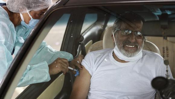 Un hombre recibe una inyección de la vacuna de Sinovac contra el coronavirus en su auto en Brasilia, Brasil, el jueves 11 de marzo de 2021. (AP Foto/Eraldo Peres).