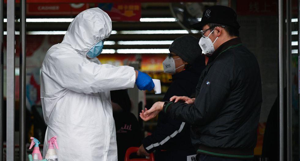 Un trabajador de un supermercado que usa traje protector toma la temperatura a un cliente en Beijing, la capital de China, país afectado por el coronavirus. (AFP).