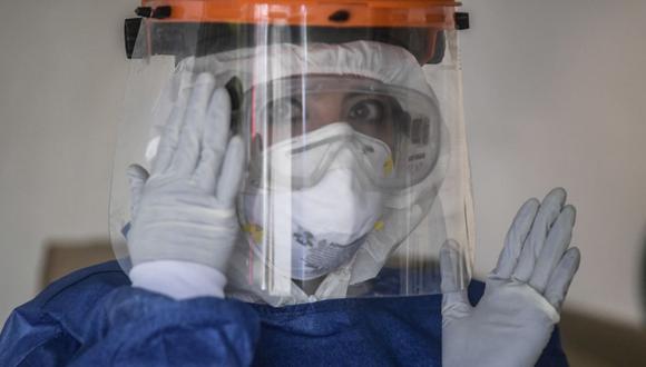 Una trabajadora de la salud del gobierno de Ciudad de México se prepara para realizar la prueba de COVID-19 en el barrio de Tlatelolco. (Foto de Pedro PARDO / AFP).