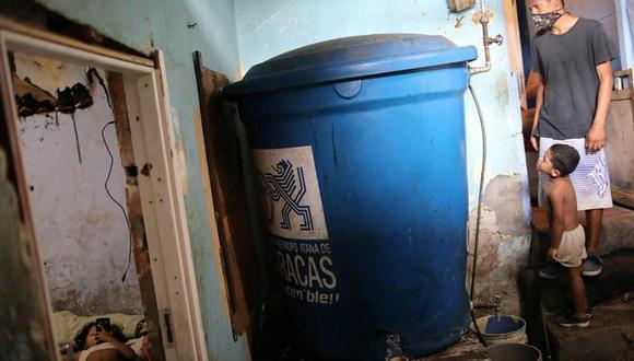 Dentro de su casa, Henry revisa el nivel del agua de su tanque de plástico, lleno de agua por un sistema de tuberías hecho por la comunidad que extrae el agua que se acumuló en la construcción de un túnel, cerca de la montaña El Ávila, que limita con la ciudad de Caracas, Venezuela. 8 de agosto de 2020. (REUTERS/Manaure Quintero).