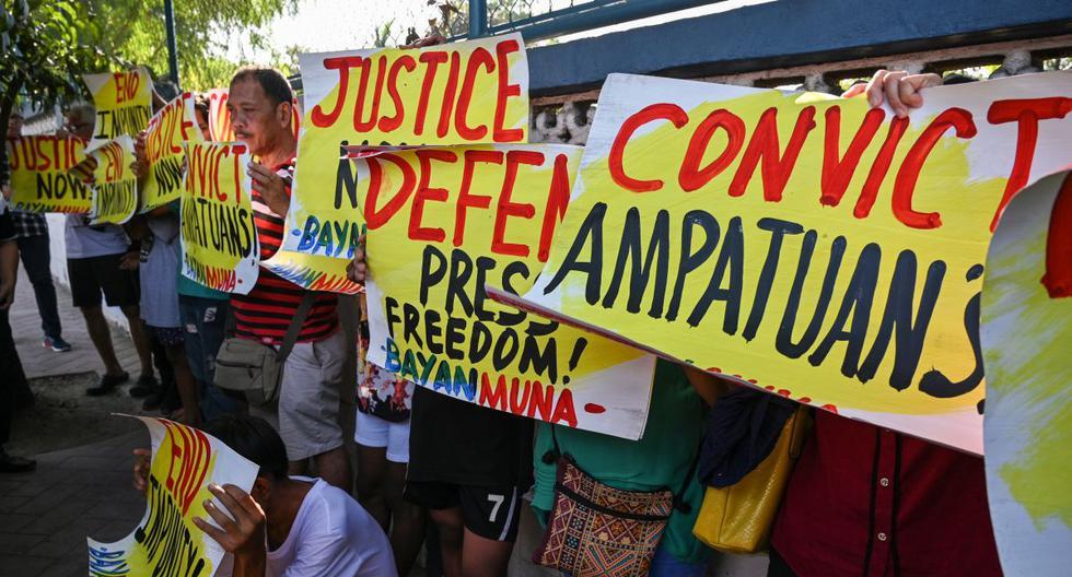 Partidarios y periodistas realizan una manifestación frente a la puerta de la sede del comando capital en Manila antes de un veredicto judicial sobre la masacre de Maguindánao. (AFP)