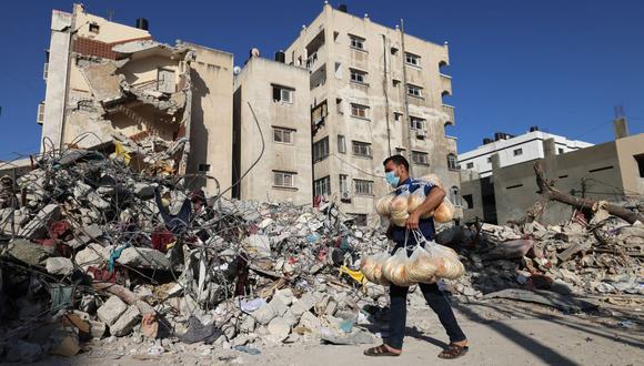 Un panadero palestino camina junto a las ruinas de un edificio destruido durante los recientes ataques de Israel en la ciudad de Gaza. (Foto de MOHAMMED ABED / AFP).