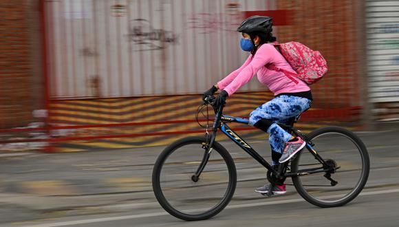 Una mujer usa una máscara facial como medida preventiva contra la propagación del nuevo coronavirus, COVID-19, monta una bicicleta en Cali, Colombia. (AFP / Luis ROBAYO).