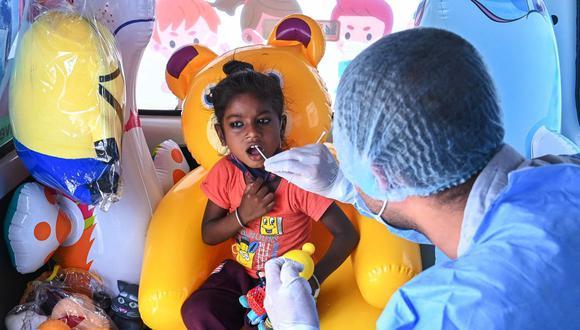 Un trabajador médico toma una muestra de hisopo de una niña para probar el coronavirus, en Nueva Delhi (India), el 1 de julio de 2021. (Prakash SINGH / AFP).