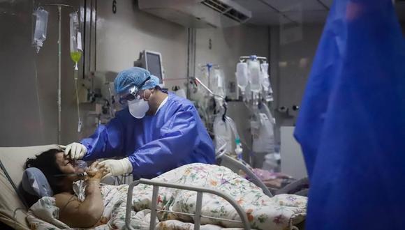 Un trabajador de la salud atiende a una paciente covid-19 en la Unidad de Cuidados Intensivos (UCI) del Hospital de Clínicas, en San Lorenzo, Paraguay. (Foto: EFE/Nathalia Aguilar).