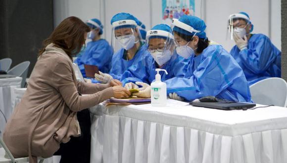 Los trabajadores médicos recopilan información de un periodista extranjero (izquierda) que espera ser inoculado con la vacuna Covid-19, en una clínica improvisada para vacunar a periodistas extranjeros que trabajan en la capital, en el Museo de Planificación Urbana de Chaoyang en Beijing. (Foto: AFP / Noel Celis).
