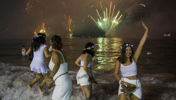 En esta imagen de archivo tomada el 31 de diciembre de 2019, un grupo de mujeres observa los tradicionales fuegos artificiales de Año Nuevo en la playa de Copacabana en Río de Janeiro. (Foto: DANIEL RAMALHO / AFP).