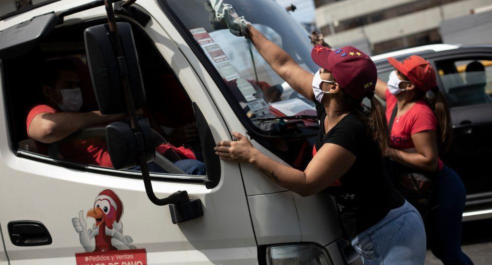 Dos ciudadanas venezolanas limpian el parabrisas de un camión en Lima durante el estado de emergencia, el pasado 16 de abril. (Foto: Joel Alonzo/GEC).