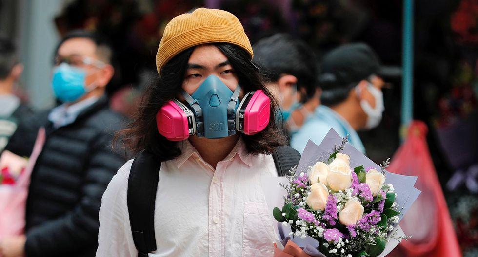 Un hombre usa una máscara de gas mientras sostiene un ramo de flores, luego del brote del nuevo coronavirus. (Foto: Reuters)