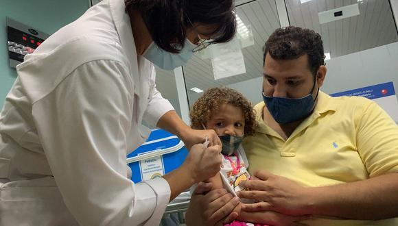 Pedro Montano holds his daughter Roxana Montano, 3, while she is being vaccinated against COVID-19 with Cuban vaccine Soberana Plus, on August 24, 2021 at Juan Manuel Marquez hospital in Havana, as part of the vaccine study in children and adolescents. (Photo by ADALBERTO ROQUE / AFP)