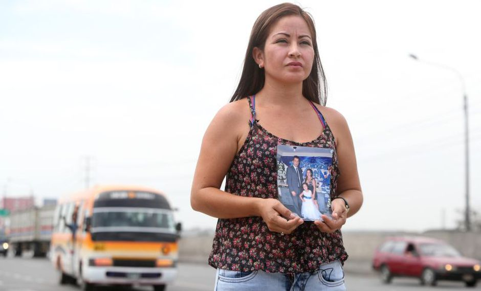 Marilyn Alvarado, la viuda de Geovanny Guzmán, sostiene un retrato de su marido en el mismo lugar donde encontró la muerte. Detrás de ella, una combi de La Nueva Estrella. (Victor Gonzales Vera / El Comercio)