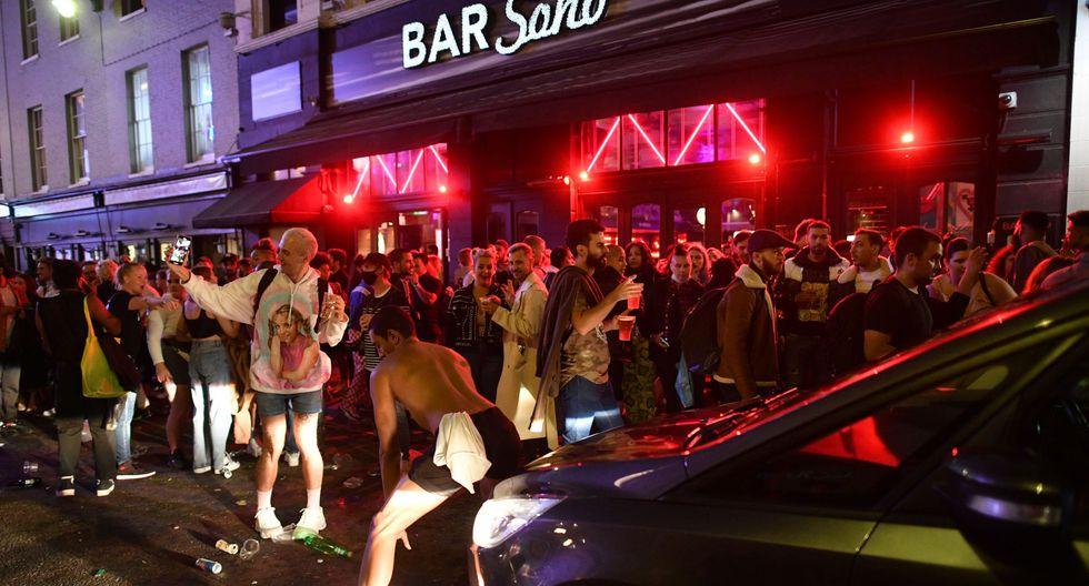 Un automóvil intente avanzar por una calle llena de juerguistas que beben en el área de Soho de Londres. Inglaterra autorizó la reapertura de los pubs que estuvieron cerrados a consecuencia de la pandemia de coronacirus. (Foto por JUSTIN TALLIS / AFP).