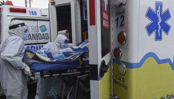 Trabajadores de la salud empujan una camilla con un paciente a una ambulancia mientras la trasladan al Hospital General de Medellín, en medio de la pandemia de COVID-19, en Medellín. (Foto: AFP / JOAQUIN SARMIENTO).