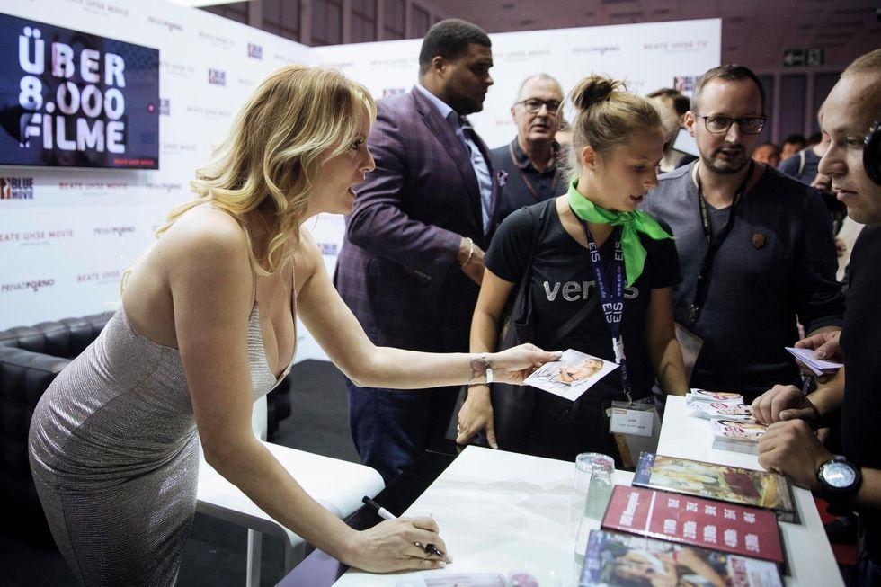 Stormy Daniels firma autógrafos durante la feria erótica Venus que se celebra en Berlín. (EFE).