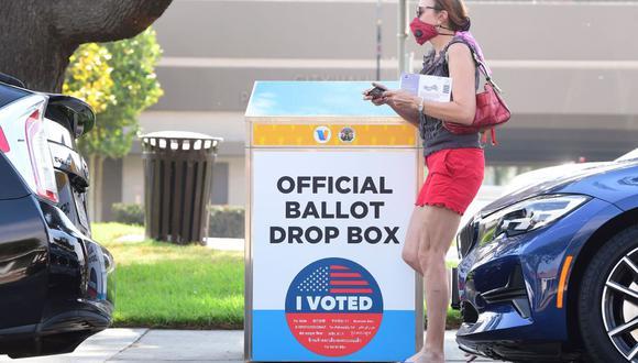 Una mujer que sostiene su boleta pasa junto a un buzón de votación por correo para las elecciones en Estados Unidos de 2020 en Monterey Park, California. (AFP / Frederic J. BROWN).