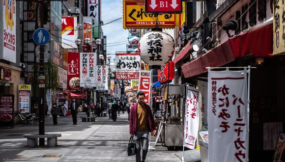 Un hombre camina en el área de Dotonbori de Osaka, Japón, el 16 de abril de 2021, en medio de la pandemia de coronavirus. (Foto de Philip FONG / AFP).