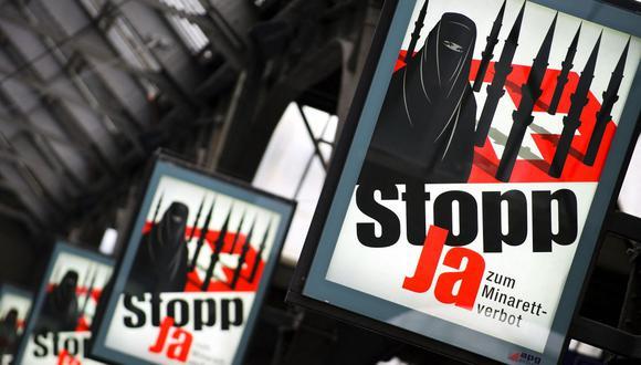 Carteles de la campaña del Partido Popular Suizo de extrema derecha que representan a una mujer con una burka sobre un fondo de una bandera de Suiza sobre la cual se ve a varios minaretes que se asemejan a misiles. (Foto de FABRICE COFFRINI / AFP).