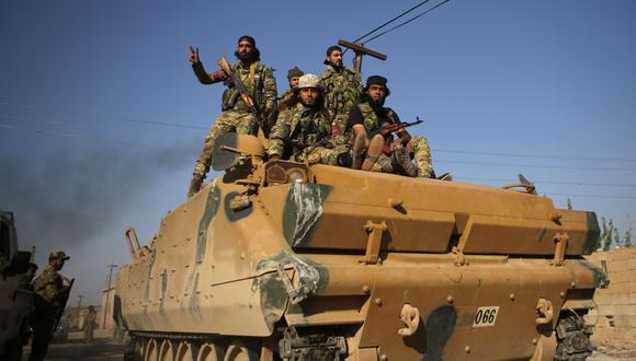 Combatientes sirios respaldados por Turquía avanzan en un vehículo blindado en los vecindarios del suroeste de la ciudad siria fronteriza de Tal Abyad. (AFP / Bakr ALKASEM).