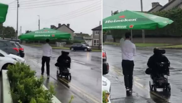 El momento en que un camarero sostiene una gran sombrilla para proteger de un aguacero a un cliente en silla de ruedas. (Foto: The Pines Cafe Bar / Facebook)