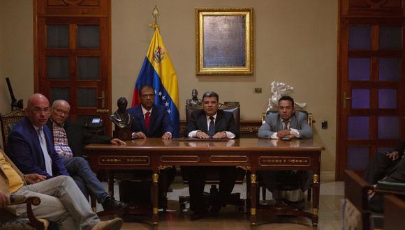 Luis Parra, al centro, junto a Franklyn Duarte (derecha) y José Noriega después de jurar como integrantes de la nueva mesa directiva de la Asamblea Nacional de Venezuela. (Foto AP / Andrea Hernández Briceño).