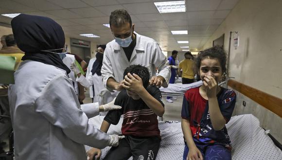 Niños miembros de la familia palestina Abu Dayer lloran en el hospital Al-Shifa después de la muerte de varios de sus parientes en un ataque aéreo de Israel contra su casa en la ciudad de Gaza. (Foto de MAHMUD HAMS / AFP).