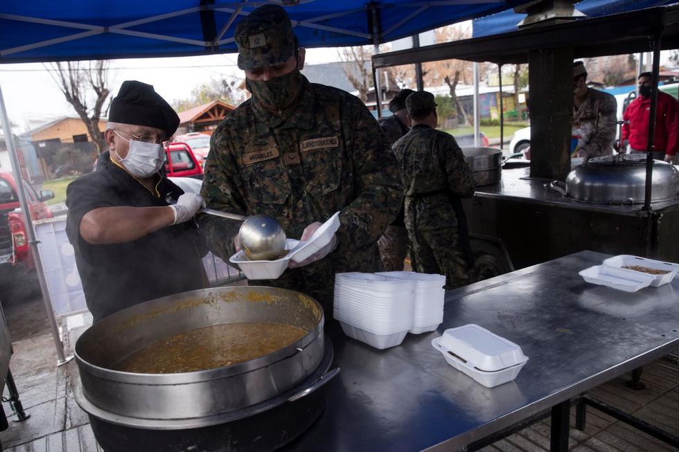 Miembros del Ejército de Chile preparan almuerzos para los vecinos vulnerables de la comuna de Las Condes este martes, en Santiago. (EFE/Alberto Valdés).
