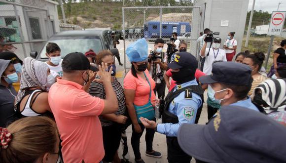 Familiares de reclusos del penal de alta seguridad La Tolva conversan con la policía durante las peleas entre los presos del Barrio 18 y la pandilla rival MS-13, en Moroceli, Honduras. (Foto: REUTERS / Fredy Rodríguez).