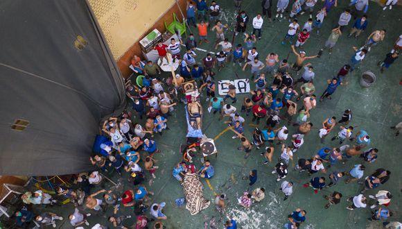 Los reclusos se reúnen alrededor de los cadáveres de dos reclusos durante un motín en la prisión de Miguel Castro Castro, en Lima, Perú. (Foto AP / Rodrigo Abd).