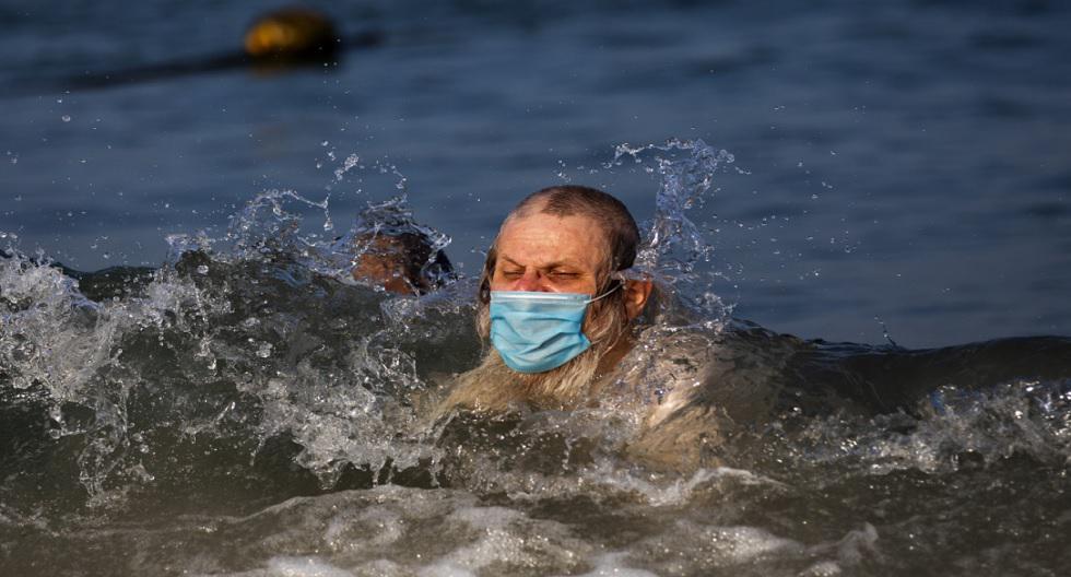 Un hombre judío ultraortodoxo, con una mascarilla, nada en el mar Mediterráneo, en una playa segregada para hombres tres días a la semana, en Tel Aviv (Israel). (Foto: Oded Balilty / AP)