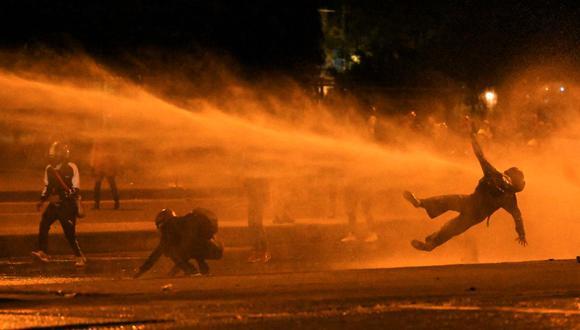Un manifestante cae al ser alcanzado por un cañón de agua durante los enfrentamientos con la policía antidisturbios en Bogotá el 12 de junio de 2021. (Juan BARRETO / AFP).